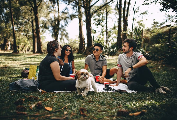 4 people and a dog having a picnic in the park
