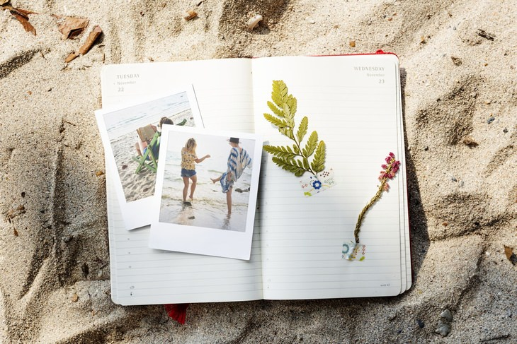 a journal with pictures and dried herbs laying on the beach
